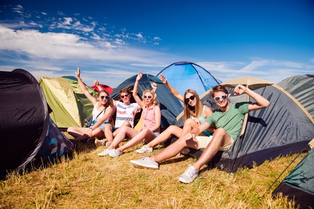 Group of teenage boys and girls at summer music festival, sitting on the ground in front of tents Фото со стока