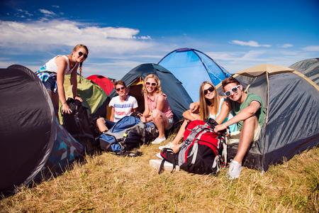niño con mochila: Grupo de adolescentes y niñas en el festival de música de verano, sentado en el suelo delante de tiendas de campaña, el embalaje
