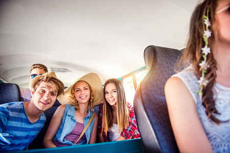 roadtrip: Teenage boys and girls inside an old campervan on a roadtrip, sunny summer day