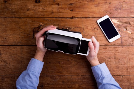 VIRTUAL REALITY: Hands of man holding virtual reality goggles and smart phone. Flat lay. Studio shot on wooden background. Stock Photo