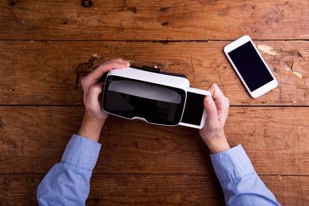 Mãos do homem que prendem óculos de realidade virtual e telefone inteligente. lay plana. O estúdio disparou no fundo de madeira. Banco de Imagens