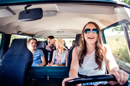 roadtrip: Teenage boys and girls inside an old campervan on a roadtrip, girl driving, sunny summer day Stock Photo