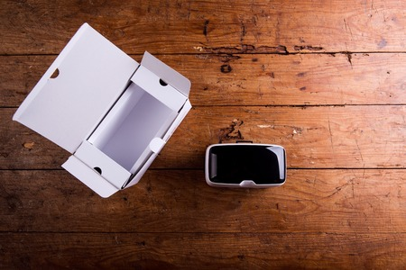 Virtual reality goggles with paper box laid on a table. Flat lay. Studio shot on wooden background. Stock Photo