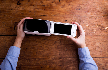 Hands of man holding virtual reality goggles and smart phone. Flat lay. Studio shot on wooden background. Stock fotó