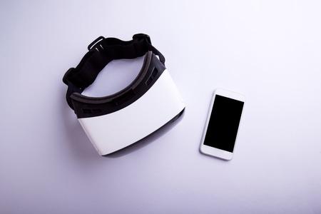 Virtual Reality Brille und Smartphone auf einen Tisch gelegt. Wohnung lag. Studio shot auf grauem Hintergrund. Standard-Bild - 54233056