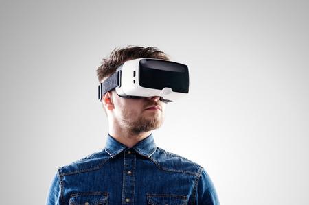 Hipster Mann in Jeanshemd Virtual-Reality-Brille tragen. Studio shot auf grauem Hintergrund Standard-Bild - 54233061