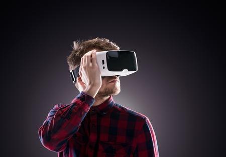仮想現実を着ているチェックのシャツで流行に敏感な人はゴーグル、それらを保持します。黒の背景で撮影スタジオ