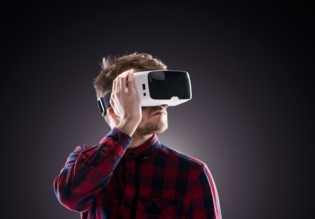 reality: Hipster man in checked shirt wearing virtual reality goggles, holding them. Studio shot on black background