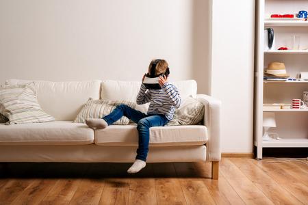 Kleiner Junge im gestreiften T-Shirt mit der virtuellen Realität Brille trägt, in einem Wohnzimmer auf weißer Couch sitzt Standard-Bild - 54233066