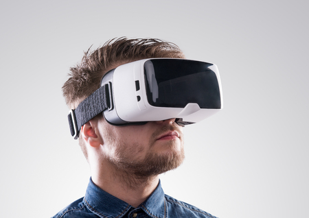 Hipster man in denim shirt wearing virtual reality goggles. Studio shot on gray background Stock Photo