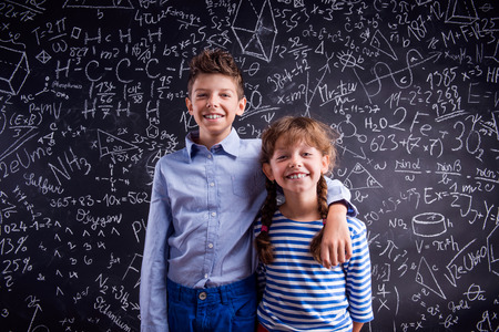 Cute boy and girl at school in front of a big blackboard. Studio shot on black background.