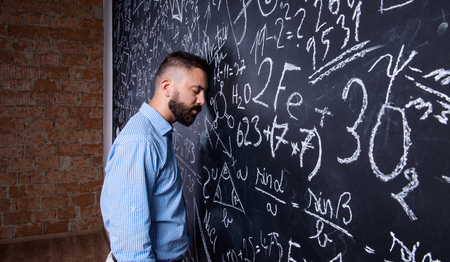 exhausted: Tired hipster teacher standing and sleeping against big blackboard with mathematical symbols and formulas. Studio shot on black background.