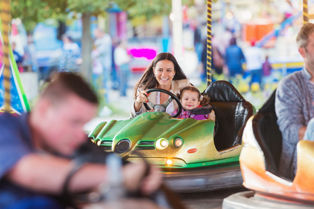 Cute little girl with her mother having fun at fun fair, driving a bumper car, amusement park Banque d'images