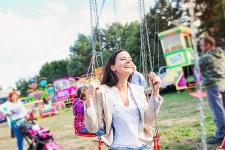 chain swing ride: Young mother with her daughter having fun at fun fair, chain swing ride, amusement park
