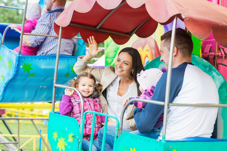 amusement park ride: Cute little girls with their mother and father enjoying ride at fun fair, young family, amusement park Stock Photo