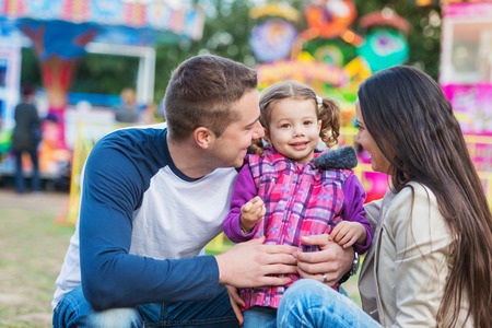fun fair: Father, mother and daughter having fun in amusement park, fun fair Stock Photo
