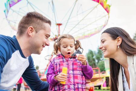 mom dad: Padre, madre e hija soplar burbujas, familia en el parque de atracciones, parque de atracciones