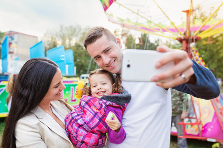 family in park: Father, mother and daughter in amusement park taking selfie, family at fun fair