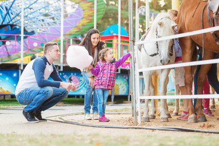 Moeder, vader en dochter met suikerspin strelen pony in pretpark, familie bij kermis Stockfoto