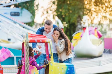 fun fair: Parents at fun fair, waving their child taking ride, amusement park Stock Photo