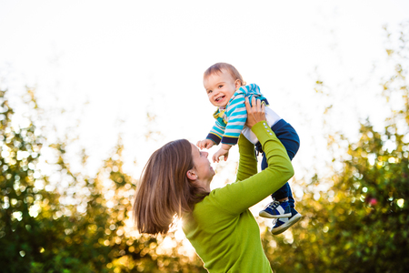 mothering: Mother holding her little son, throwing him in the air, green tree Stock Photo