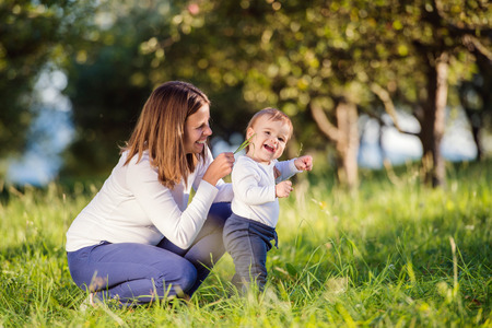 family tickle: Mother holding her little son making first steps outside in green sunny nature, tickeling him with grass