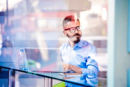 young businessman: Hipster manager sitting in cafe by the window working on laptop, street reflection Stock Photo