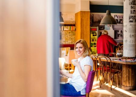 jovenes estudiantes: Mujer rubia en café moderno de la ciudad que se sienta en la tabla que bebe el café