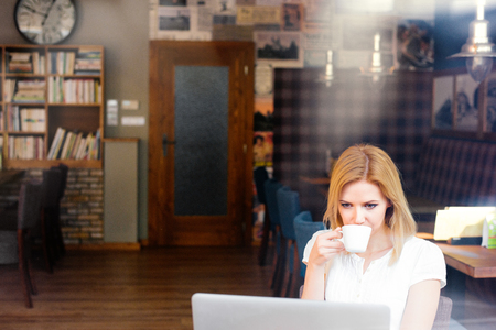 girl with laptop: Blond woman with notebook in cafe sitting at the table drinking coffee
