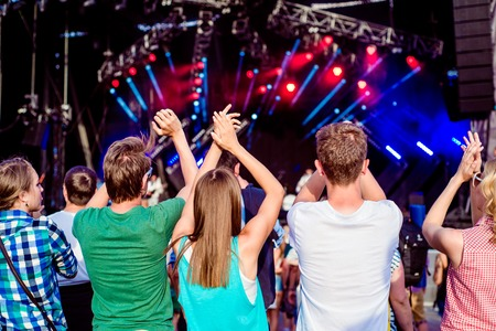 Teenagers at summer music festival against the stage in a crowd enjoying themselves, clapping, back view Stock Photo