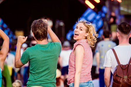 Teenagers at summer music festival against the stage in a crowd enjoying themselves, dancing and singing, back view