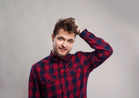 male hair: Hipster man in red checked shirt smiling, scratching head. Studio shot on gray background