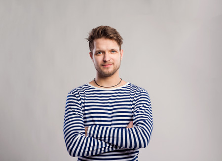 sleeve: Hipster man in striped black and white long sleeve t-shirt. Studio shot on gray background
