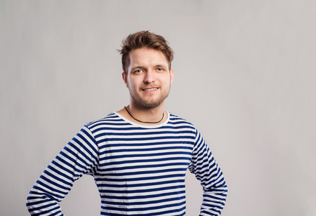 smile face: Hipster man in striped black and white long sleeve t-shirt. Studio shot on gray background