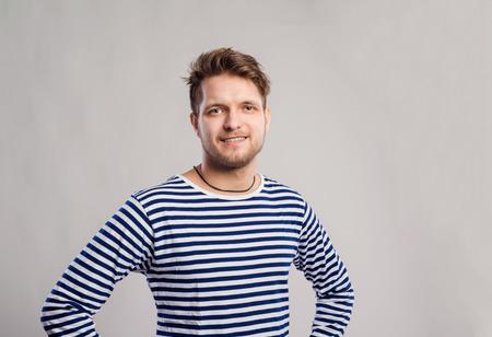 viso uomo: uomo Hipster in strisce manica lunga t-shirt in bianco e nero. Studio girato su sfondo grigio