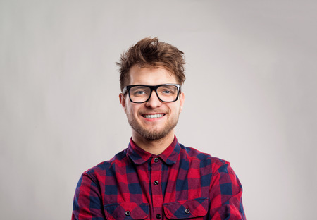 man shirt: Hipster man in red checked shirt and eyeglasses. Studio shot on gray background Stock Photo