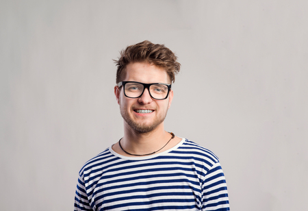 white long sleeve: Hipster man in striped black and white long sleeve t-shirt and eyeglasses. Studio shot on gray background Stock Photo