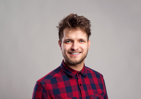 one man: Hipster man in red checked shirt smiling. Studio shot on gray background Stock Photo