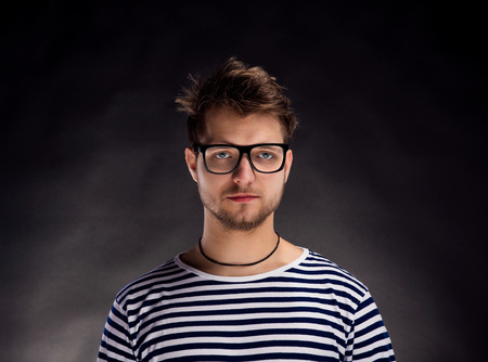 white long sleeve: Hipster man in striped black and white long sleeve t-shirt and eyeglasses. Studio shot on black background Stock Photo