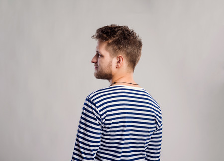 white long sleeve: Hipster man in striped black and white long sleeve t-shirt. Studio shot on gray background, back view.