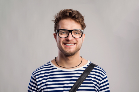 long sleeve: Hipster man in striped black and white long sleeve t-shirt and eyeglasses. Studio shot on gray background Stock Photo