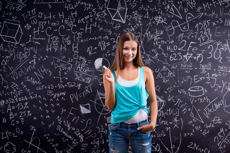 singlet: Thinking girl  in blue singlet holding her head against big blackboard with mathematical symbols and formulas, back view, rear view