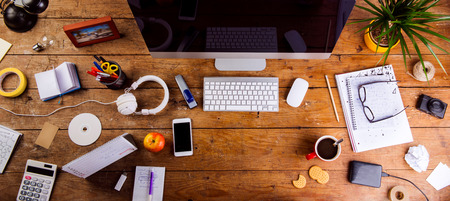 Biurko z różnymi gadżetami i artykułami biurowymi. Komputer, smartfon i inne urządzenia oraz materiały piśmienne w całym miejscu pracy. Płaskie leże. Skopiuj miejsce. Zdjęcie Seryjne
