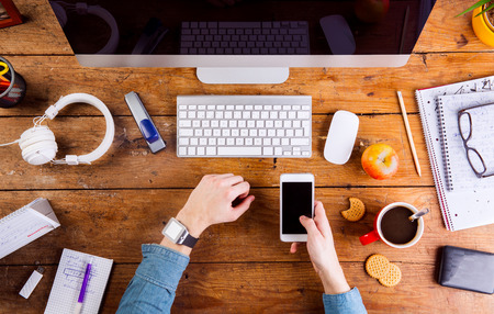hand lay: Business person working at office desk. Smart watch on hand, holding a smart phone. Coffee cup, notepad and eyeglasses and various office supplies around the workplace. Flat lay. Stock Photo