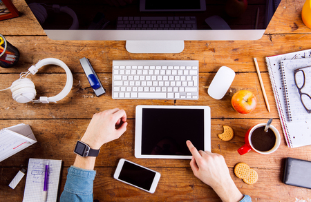 hand lay: Business person at office desk. Smart watch on hand,  working on tablet. Coffee cup, notepad and eyeglasses and various office supplies around the workplace. Flat lay.