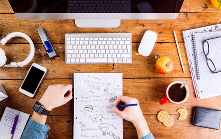 hand lay: Business person at office desk writing and working. Smart watch on hand and smart phone on the table. Coffee cup, notepad and eyeglasses and various office supplies around the workplace. Flat lay. Stock Photo