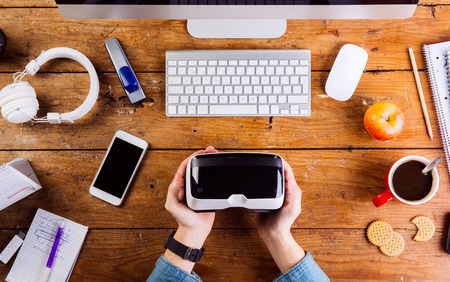 hand lay: Business person working at office desk. Smart watch on hand, holding a virtual reality goggles. Various office stuff  around the workplace. Flat lay. Stock Photo