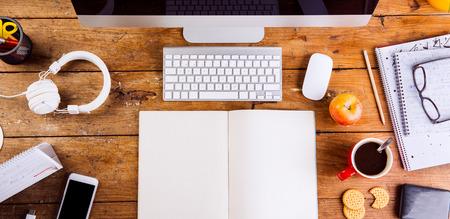 Escritorio con el cuaderno vacío varios adminículos y suministros de oficina. Ordenador, teléfono inteligente y papelería alrededor del lugar de trabajo. Lecho plano. Copie el espacio.