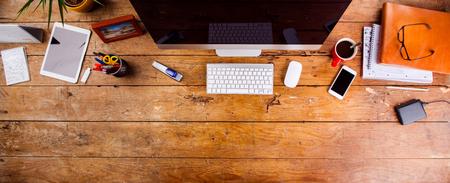 Письменный стол с различными устройствами и канцелярских принадлежностей. Компьютер, смартфон и канцелярские вокруг рабочего места. Плоский лежал. Копирование пространства.