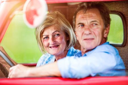 uomo rosso: Primo piano di coppia senior all'interno di un camioncino rosso, uomo con in mano un volante Archivio Fotografico